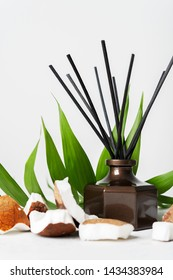 Aroma reed diffuser bottle home fragrance with rattan sticks with the scent of coconut and the freshness of the tropics on white background with copy space.