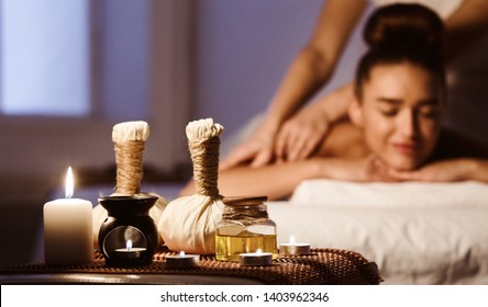 Aroma Spa. Woman Enjoying Back Massage In Luxury Spa With Candle And Herbal Balls On Foreground