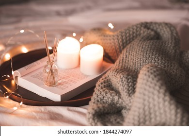Aroma sticks with liquid scented water in bottle with burning candles staying on open book and knitted textile in bed closeup over lights at background . Winter holiday season.