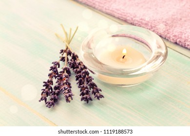 Aroma tea candle with lavender twigs on table, decor bokeh light, relaxing spa time. Toned.