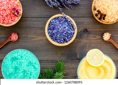 Aromas of bath salt. Lemon, coffee, rosemary, rose, lavender near bowls with colorful bath salt on dark wooden background top view