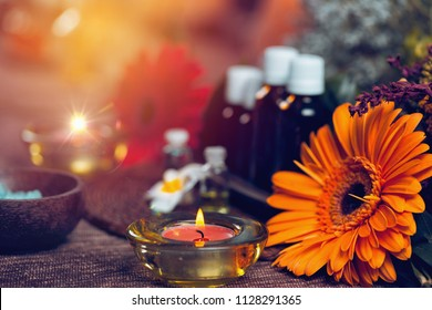 Aromatherapy composition with transparent aromatherapy bottles filled with blue and green essential oils, colorful red and orange flowers, red candles, sea salt in wooden bowl and small white flowers