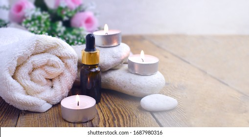 Aromatherapy concept with essential oil bottle, towel, burning candles and pebbles. Spa or herbal medicine still life compocition. Copyspace.