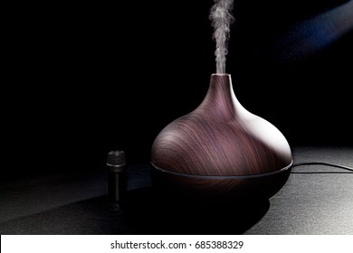 Aromatherapy. Essential oil aroma diffuser humidifier diffusing water articles in the air. Electric ultrasonic device emitting atomized water droplets against black background with copy space.