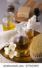 Aromatherapy essential oils in glass bottle and brush for the body with a jasmine flower.
