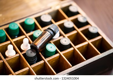 Aromatherapy essential oils in wooden box. Herbal alternative medicine with essential oils bottles in wooden box, healthy organic natural therapy