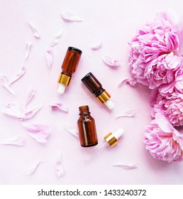 Aromatherapy essentials oils and pink peonies on a pink concrete background