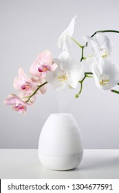 Aromatherapy at home. Ultrasonic Oil diffuser and orchid flowers on white table of gray background. Close up view with copy space