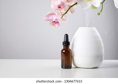 Aromatherapy at home. Ultrasonic Oil diffuser with glass amber bottle and orchid flowers on white table of gray background. Close up view with copy space