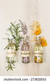 Aromatherapy massage oils. Row of essential oils in glass bottles, rosemary, lavender and calendula,  on the wooden board.