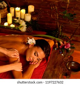 Aromatherapy massage of woman in spa salon. Girl on candles background treats problem health . Luxary interior with working masseuse. Indian back Massage as pain relief for female