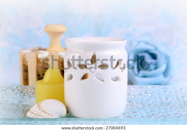 Aromatherapy set with candle, seashell, ceramic burner and oils in the background