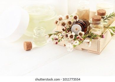 Aromatherapy set. Floral scent essential oils blend of bottles with fresh blossom, front view, light white space.