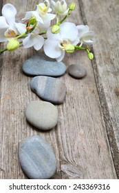 Aromatherapy spa set. Spa stones and orchid on wooden background