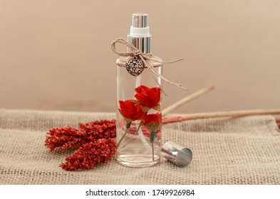 Aromatic air freshener in a transparent glass bottle with red roses inside