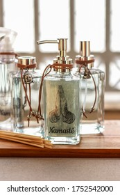 Aromatic air freshener in a transparent glass bottle with namaste symbol on label