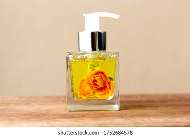 Aromatic air freshener in a transparent glass bottle with orange roses inside