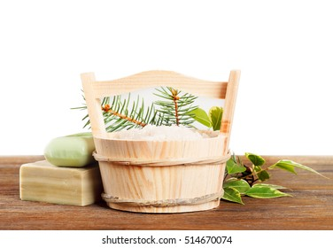 Aromatic bath salt in wooden bucket and handmade soap. Herbal soap and salt on a wooden table.