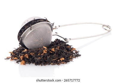 Aromatic black dry tea with petals and a tea strainer on white reflective background.