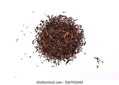Aromatic black pu-erh tea leaves, a pile of dry red chinese pu-er, close-up, isolated on white