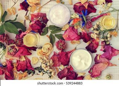 Aromatic botanical cosmetics. Dried herbs flowers mixture, facial mask in sample jars, oils. Holistic herbal DIY skincare beauty hack. Retro pink toned.