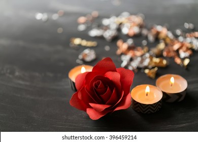 Aromatic candles on table with paper rose on shiny background