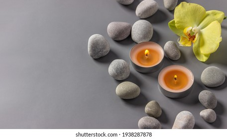 Aromatic  candles, orchid flower and stones on a gray background.  Spa composition. Relaxation and zen like concept.