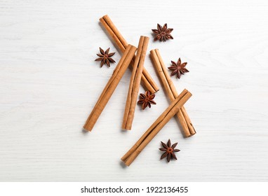 Aromatic cinnamon sticks and anise on white wooden table, flat lay