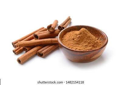 Aromatic cinnamon sticks and powder on white background
