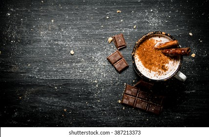 Aromatic cocoa drink with cinnamon and chocolate. On black rustic background