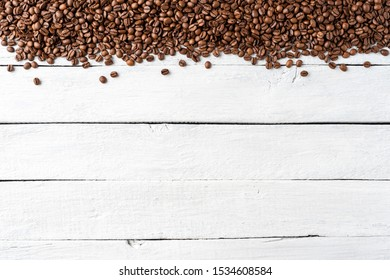 Aromatic coffee beans on white wooden table. Top view