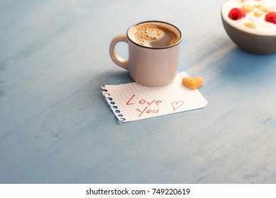 "Aromatic coffee and ""love you"" message - Mug of Arabic coffee and a heart-shaped sugar on a math paper with the love you message and a bowl of yogurt on a blue wooden table, in the morning light."