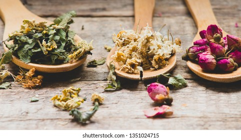 Aromatic flowers tea in spoons on rustic wooden background