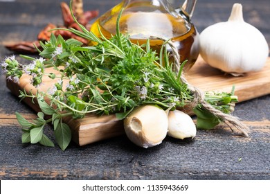 Aromatic fresh kitchen herbs, garlic, onion and olive oil, main ingredients for many dishes in medditerranean cuisine