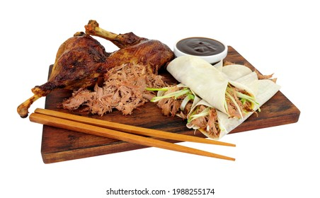 Aromatic half crispy duck with Chinese style pancakes and hoisin sauce on a wooden board isolated on a white background
