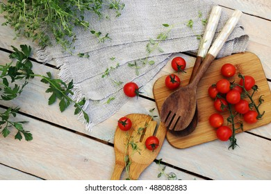 aromatic herbs and cherry tomatoes on a wooden table with kitchen utensils are