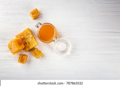 Aromatic honey in jar and honeycombs on wooden background