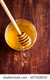 Aromatic honey with wooden honey dipper in a jar on a wooden table, selective focus, closeup. Healthy and organic food option. Image with copy space.