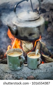Aromatic and hot coffee with kettle on campfire