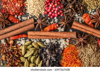 Aromatic Indian spices on a gray slate background. Herb and spice ingredients on slate. Top view. Food background. Assortment of spices