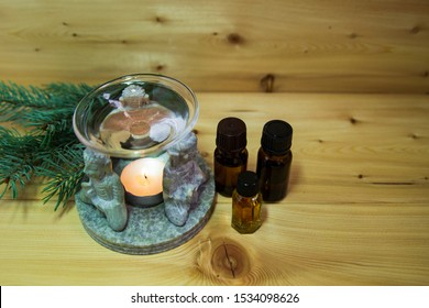 Aromatic lamp, Buda figures, pine branches, pine cones, candle, bottle of aromatic oil on the table close-up. Wooden warm background. Health. Prevention. Alternative treatment. Aromatherapy