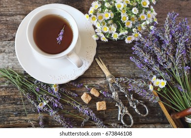 Aromatic lavender tea, fresh lavender and wild chamomile, rustic style on old wooden background. Top view