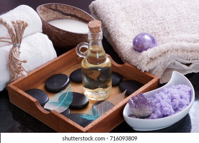 Aromatic oil with hot stones for massage in a wooden box next to towels, purple salt and milk in a coconut.