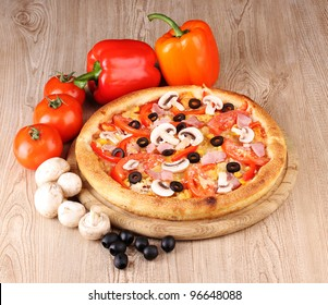 Aromatic pizza with vegetables and mushrooms on wooden background