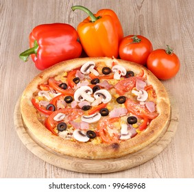 Aromatic pizza with vegetables on wooden background