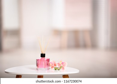 Aromatic reed air freshener and flowers on table against blurred background
