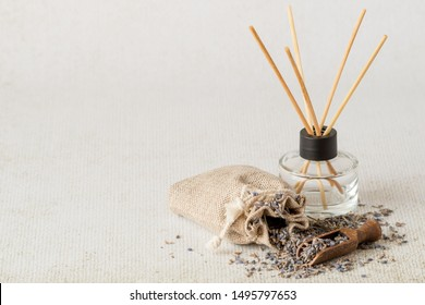 Aromatic reed air freshener and linen bag with dry lavender flowers on a light background with copy space.