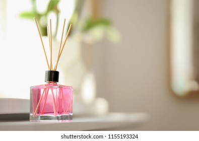 Aromatic reed air freshener on table against blurred background
