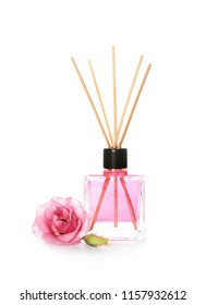 Aromatic reed air freshener and rose on white background
