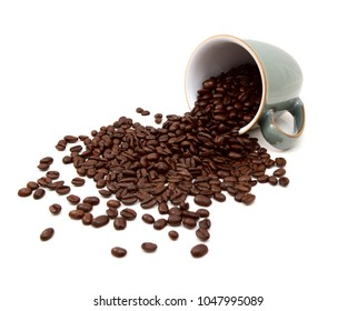 Aromatic roasted coffee beans pouring out from a green china mug on a white background